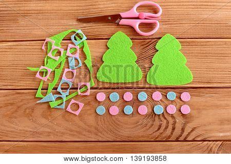 Two green felt Christmas trees, pink and blue balls set, scissors, felt scraps on a wooden table. Home Christmas tree decor crafts idea. Step. Top view