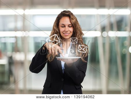 Portrait of a young smiling woman using a digital tablet. Email symbols
