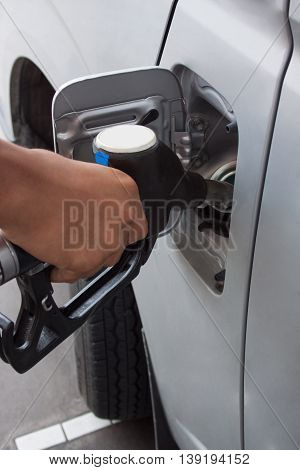 Petrol gas station pump and pumping gasoline fuel with hand