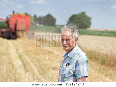 Farmer On Field With Combine Harbester