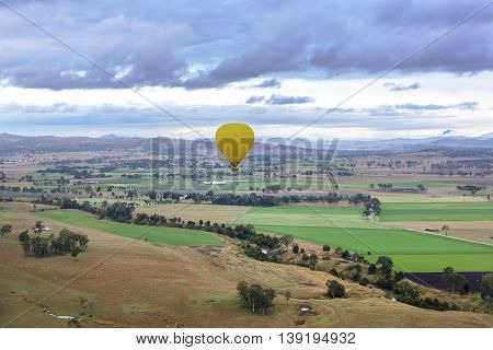 Yellow hot air balloon in the air floating across farm land on a cloudy day