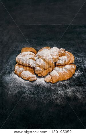 Picture of croissants with powdered sugar on grey table. Macro.