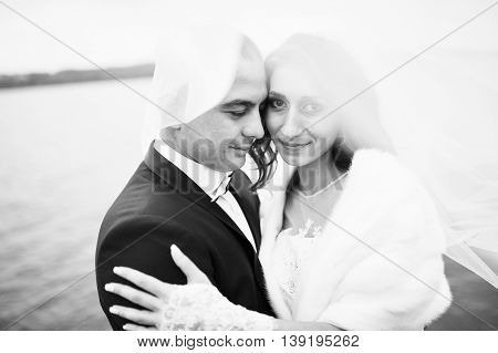 Close Up Wedding Portrait Of Couple Unde Veil In Cloudy Weather On The Background Of The Pier At The