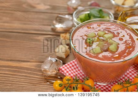 Soup gazpacho with yellow tomatoes on a brown background