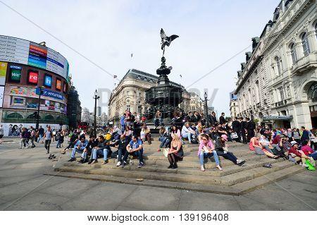 PICCADILLY CIRCUS London - June 06, 2014: People enjoying the sun at Piccadilly Circus London