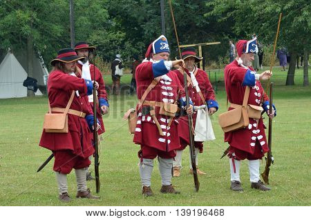 Military Tattoo COLCHESTER ESSEX UK 8 July 2014: Row of redcoat soldiers with guns in recreation