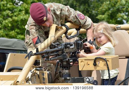 Military Tattoo COLCHESTER ESSEX UK 8 July 2014: Small Girl being shown machine gun by soldier