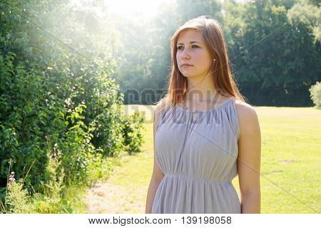 young woman enjoying a sunny day in nature. with sun flare.
