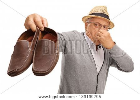 Disgusted senior holding a pair of stinky shoes isolated on white background