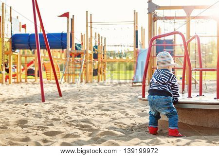 Little boy playing on playground in the spring