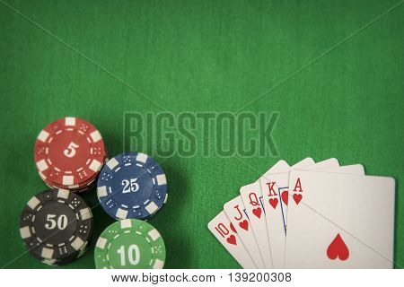 Gambling chips frame and flush royal on green card table background