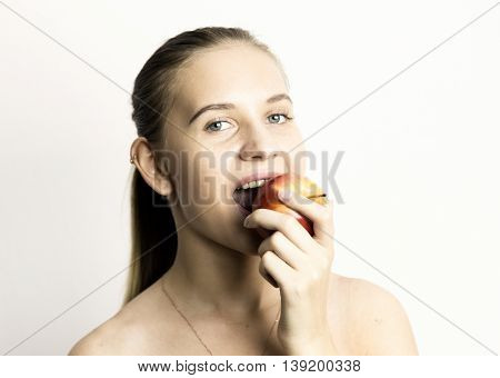 beautiful naked young woman eating an apple. healthy food - strong teeth concept.