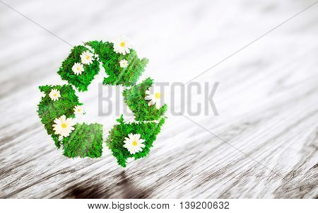 Green recycle sign with daisy flower on wooden desk. 3D illustration.