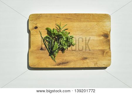 Fresh herbs on wooden cutting board. Flat lay food on white table.