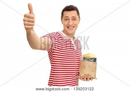 Joyful man holding a bag of potato chips and giving a thumb up isolated on white background