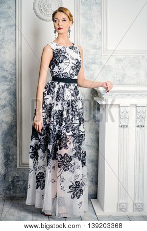 Full length portrait of a charming woman in beautiful evening dress standing by a fireplace in a room with classical vintage interior. Jewellery. Fashion shot. Hairstyle.