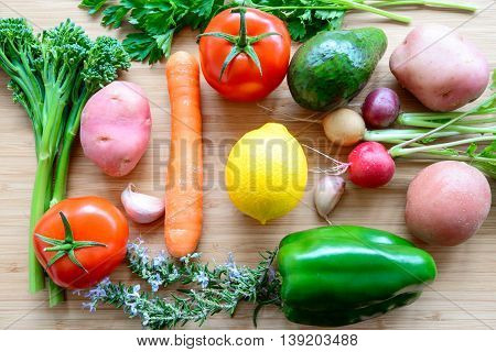 Top flat lay view of fresh organic vegetables on wooden cutting board with copyspace