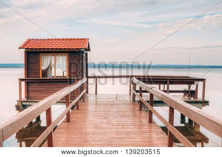 Old wooden pier for fishing, small house shed and beautiful lake or river in background. Picturesque natural landscape. Vacation concept.