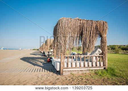 Series of bungalows on the sandy shore with wooden walkway and sea on the background