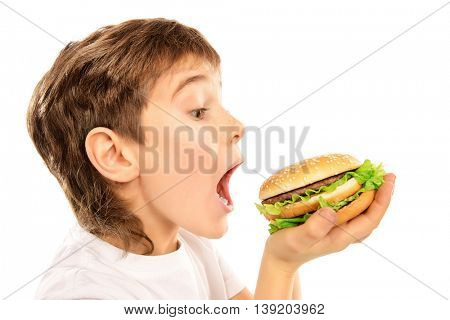 Happy nine year old boy  eating burger with appetite. Fast food. Concept of healthy and unhealthy food. Isolated over white.