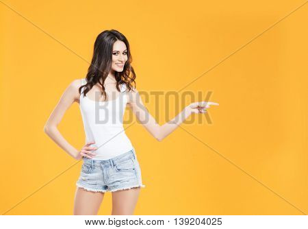 Young and gorgeous woman with a perfect body in jeans and shirt. Fashion model posing in studio.