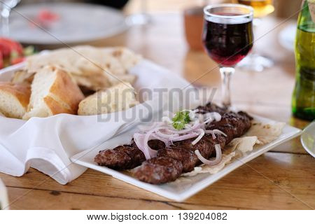 Traditional delicious kebab with onion and glass of wine