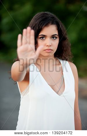 Serious brunette girl making stop sign in the park