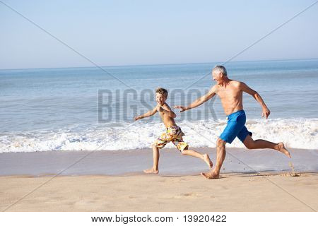 Grandfather chasing young boy on beach