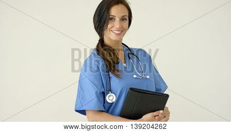 Woman in scrubs holds black portfolio and smiles