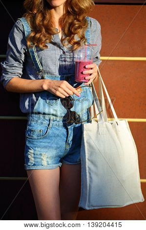 Woman Hipster With Smoothies In Disposable Cup, Linen Bag And Sunglasses Keep In Their Hands