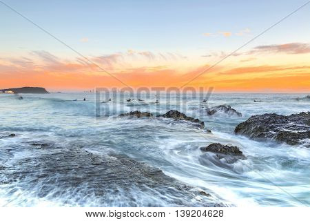 High tide over the rocks and surfers at Currumbin Rock during colourful sunrise, Gold Coast