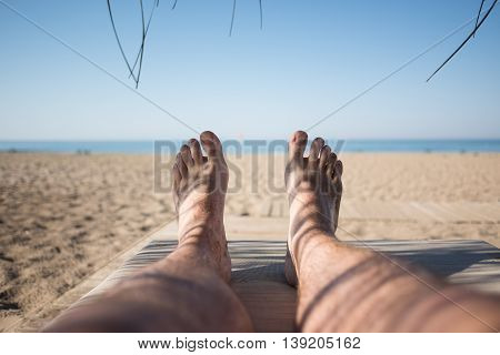Men's feet on lounge first person view from bungalow on the sea with sand beach