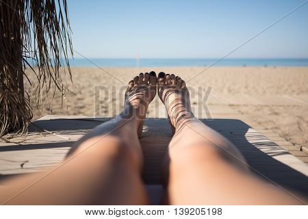 Women feet on lounge first person view from bungalow on the sea with sand beach