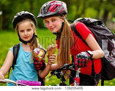 Girls sisters wearing bicycle helmet and gloves with rucksack rides bicycle. Girls children are bicycling in summer park. Happy girls biking eating ice cream cone .
