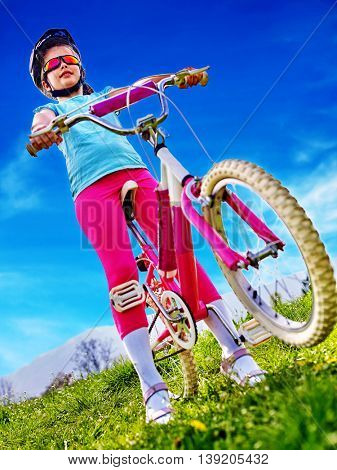 Bicycle child. Child wearing bicycle helmet rides bicycle and look at blue sky. Child girl in cycling. Bicycling is good for child health. Green grass in summer park.