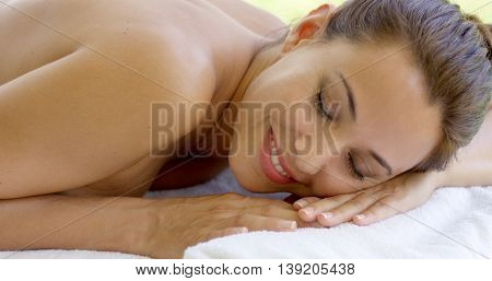 Woman relaxing on spa table  outdoor patio