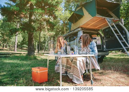 Young woman playing harmonica sitting in campsite with her female friend. Leisure time and enjoyment concept.