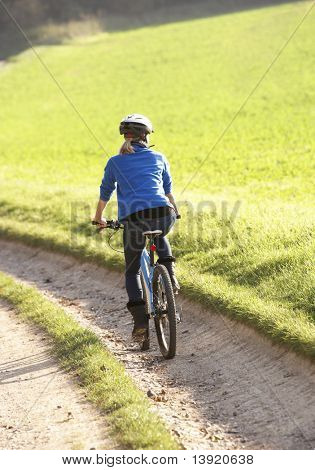 Young woman rides her bike in park