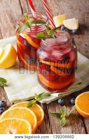 Sangria With Fruit And Berries, Ice And Mint Close Up In A Glass Jar. Vertical
