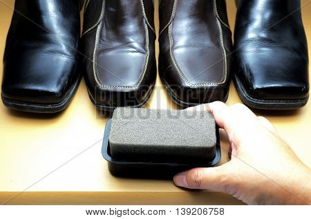 Shoe polishing brush with hand, brown and black leather shoes on wooden floor. Focus on polishing brush.  Defocus on shoes. Space for texts.