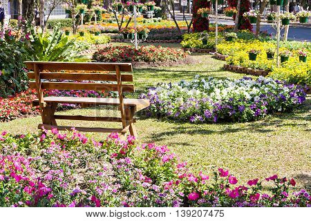 Wooden Bench In The Colorful Flower Garden