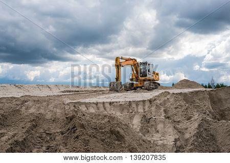 Yellow excavator on a heap of sand at quarry