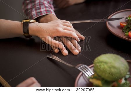Happy couple eating vegan dishes in vegan restaurant or cafe. Closeup picture of man and woman holding each other's hands.