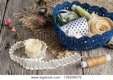 Colored ribbons and spools of thread in blue openwork basket on sackcloth and on gray wooden table.