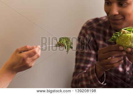 Portrait of lady eating vegan dish and feeding her boy-friend. Happy couple spending free time in vegan restaurant or cafe.