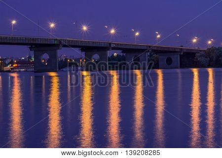 Night bridge lights reflected in river waters. HDR