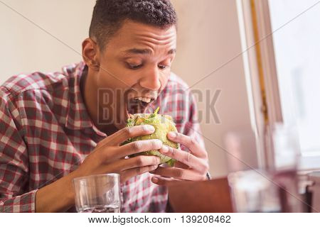 Picture of hungry man eating vegan burger in vegan restaurant or cafe. Handsome man following vegan diet.