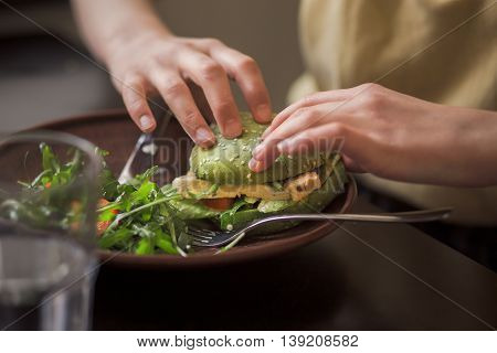 Picture of vegan dish represented on wooden plate. Lady's hands taking vegan burget from plate in vegan restaurant or cafe.