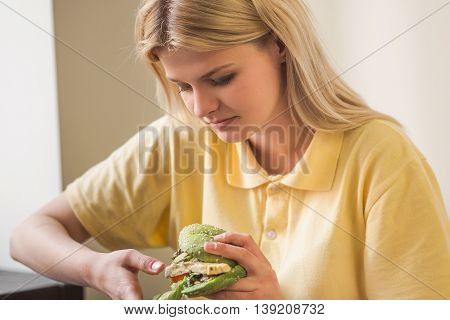 Picture of blond woman looking at vegan burger in vegan restaurant or cafe. Beautiful lady in yellow t-shirt havig lunch or dinner.
