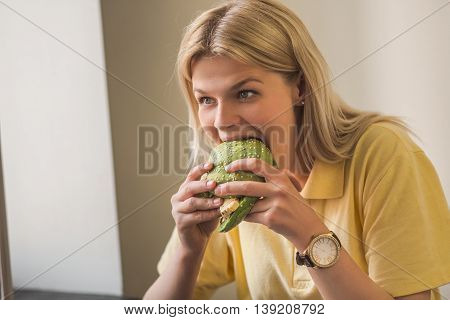Closeup picture of hungry lady eating healthy food. Vegan concept. Image of beautiful woman eating vegan burger in vegan restaurant or cafe.